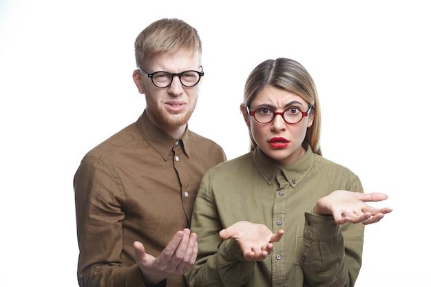 Dois funcionários usando óculos com expressões de desagrado, fazendo caretas e gesticulando em confusão, sentindo-se frustrados. colegas confusos do sexo masculino e feminino pedindo explicações, olhando