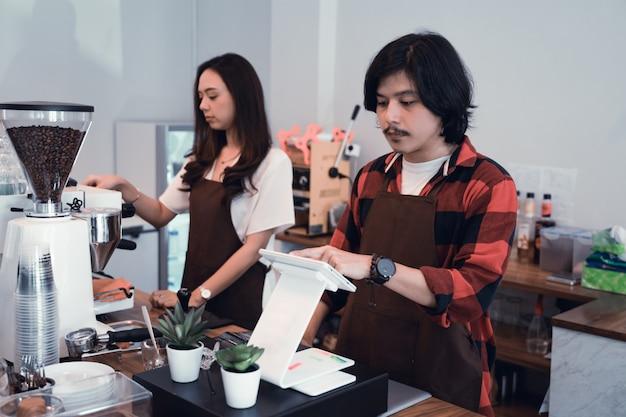 Dois garçom de café e barista trabalhando