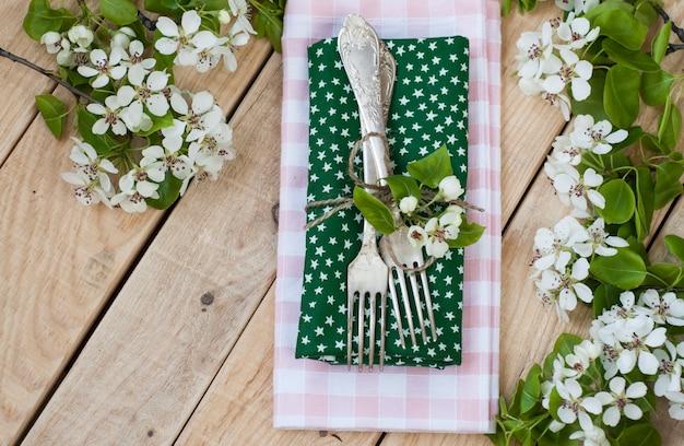 Dois garfos na superfície de madeira rústica e galhos com flores