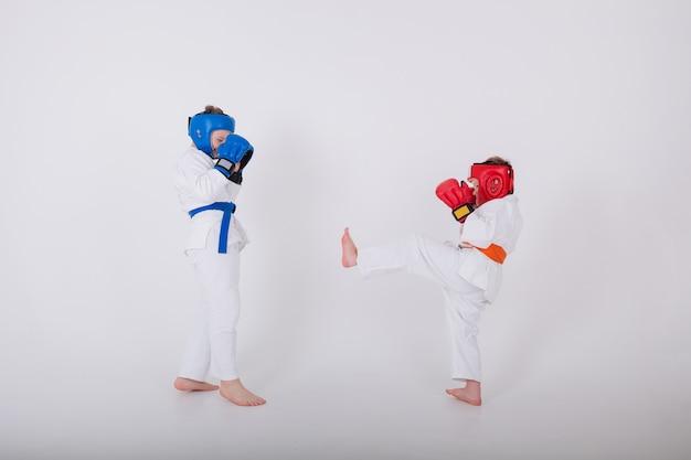 Dois garotinhos em um quimono branco, capacete e luvas competem em uma parede branca