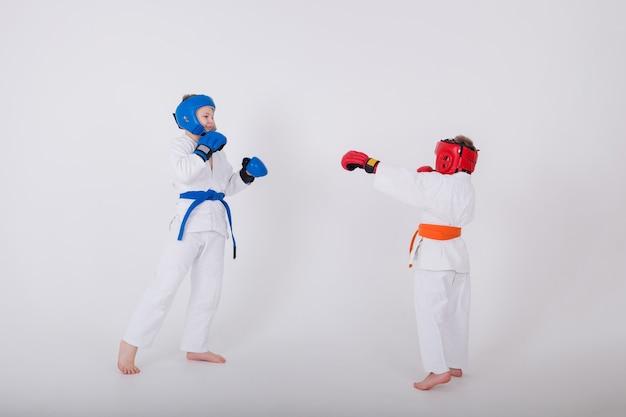 Dois garotinhos em um quimono branco e usando um capacete com luvas lutando na parede branca com uma cópia do espaço