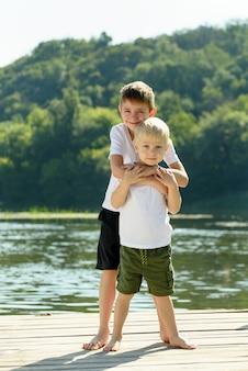 Dois garotinhos estão abraçando na margem do rio