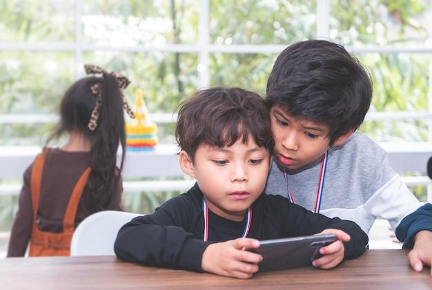 Dois garotinhos estão jogando jogo online no telemóvel