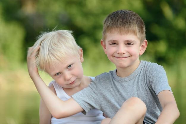 Dois garotinhos estão sentados ao ar livre. árvores verdes borradas à distância. conceito de amizade e fraternidade