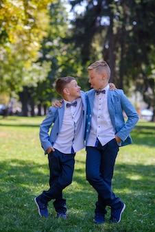 Dois garotinhos, irmãos estão vestidos de terno. as crianças estão de pé no parque e se abraçando. caras mostram linguagem um para o outro.