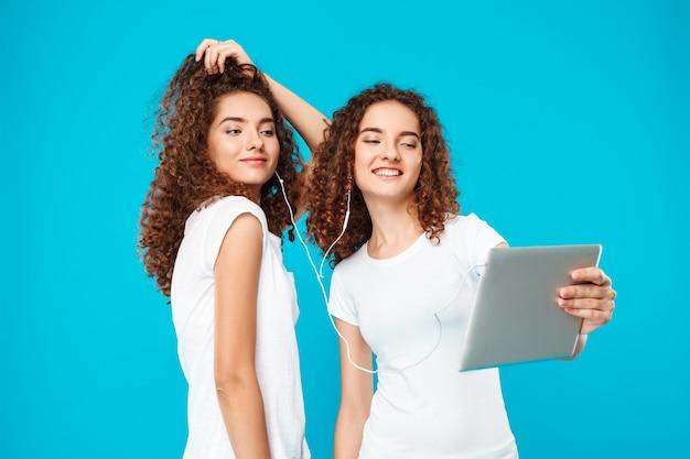 Dois gêmeos da mulher fazendo selfie sobre tablet azul.