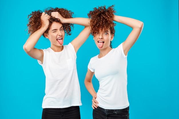 Dois gêmeos da mulher segurando o cabelo, brincando sobre azul.