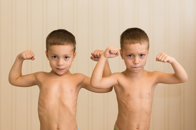 Dois gêmeos menino demonstram os músculos