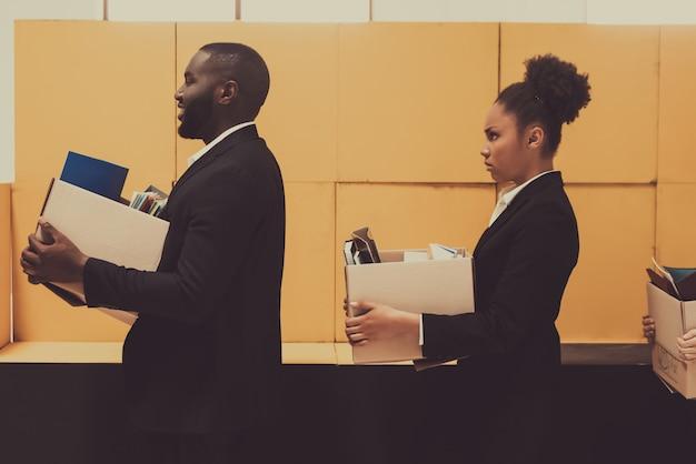 Dois gerentes afro-americanos com caixas do escritório.