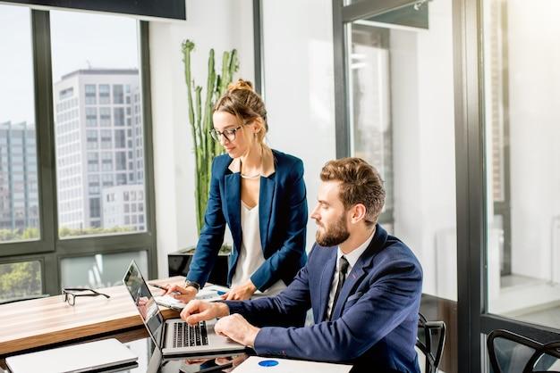 Dois gerentes de terno trabalhando juntos com laptop e documentos no interior do escritório de luxo