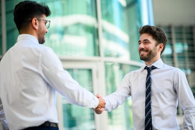 Dois gerentes se cumprimentando ao ar livre em um ambiente moderno