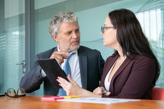 Dois gerentes sentados e conversando na sala de reuniões, usando um tablet, discutindo e analisando relatórios, discutindo