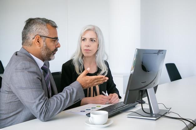 Dois gerentes sérios, assistindo a apresentação no monitor do pc, discutindo o projeto, sentado na mesa com o diagrama de papel. conceito de comunicação empresarial