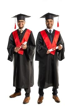 Dois graduados afro-americanos em vestido e boné