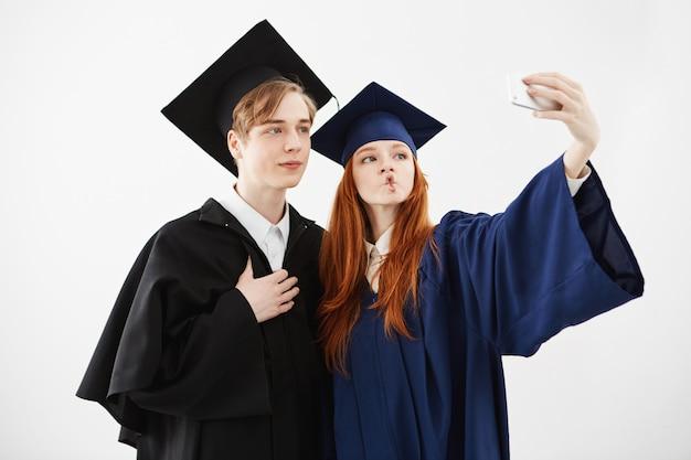 Dois graduados felizes da universidade enganando fazendo selfie.
