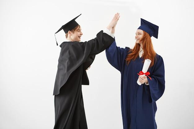 Dois graduados felizes dando cinco sorrisos depois de receber diplomas que logo serão advogados.