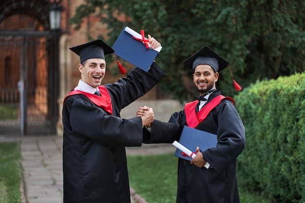 Dois graduados internacionais comemorando a formatura no campus da universidade e olhando para a câmera.