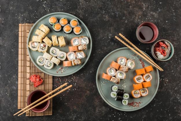 Dois grandes jogos com rolos de sushi servidos pelo chef em um fundo escuro. vista de cima com uma cópia-espaço. comida do restaurante. postura plana