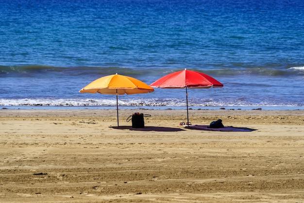 Dois guarda-chuvas solitários na praia de maspalomas área dorada nas ilhas canárias. espanha. europa.