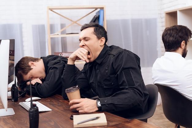 Dois guardas estão cansados para a noite um dorme outro está bocejando.