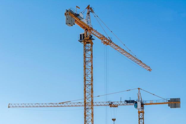 Dois guindastes de construção amarelo no fundo do céu azul