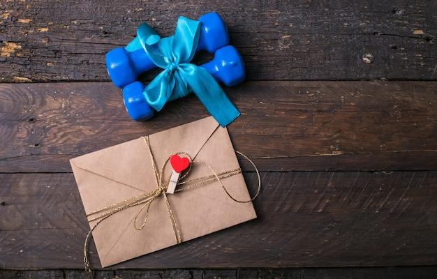 Dois halteres azuis com um laço de presente e etiqueta de papel em branco, coração em pranchas de madeira, conceito de férias esportivas