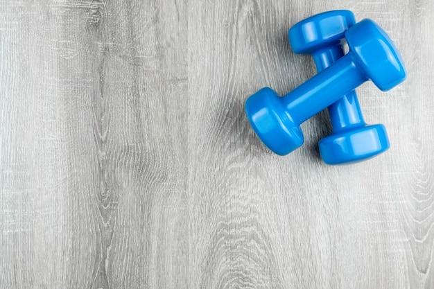 Dois halteres azuis sobre um fundo de madeira, foto do banner, vista superior, espaço para texto.