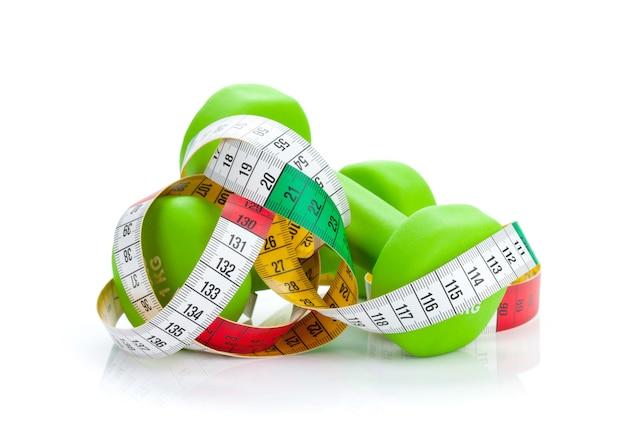 Dois halteres verdes e fita métrica. fitness e saúde. isolado em fundo branco