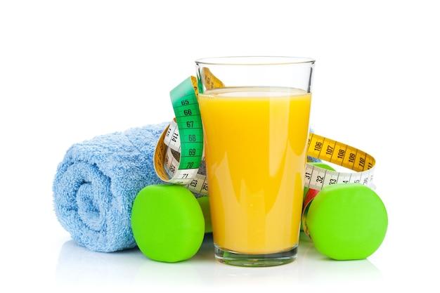 Dois halteres verdes, fita métrica e suco de laranja. fitness e saúde. isolado em fundo branco