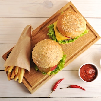 Dois hambúrgueres com batatas fritas em um saco de papel e o ketchup