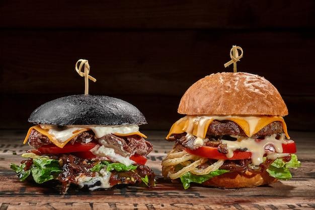 Dois hambúrgueres com rissóis de carne, queijo, cebola caramelizada, legumes e molho
