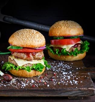 Dois hambúrgueres com uma costeleta de carne, legumes e alface verde