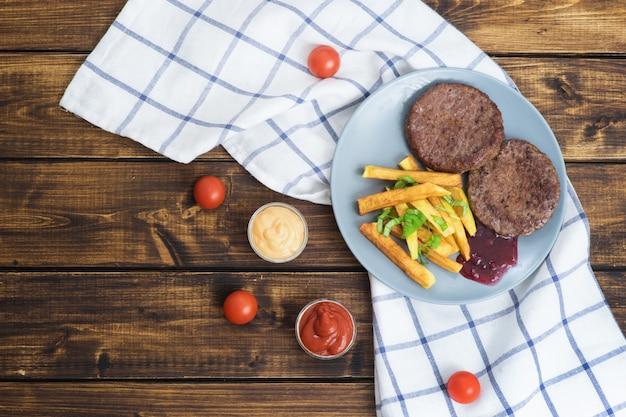 Dois hambúrgueres de carne com batatas fritas na mesa de madeira