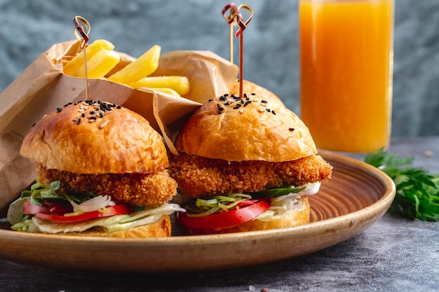 Dois hambúrgueres de mini nuggets de frango servidos com batatas fritas em caixa de papel