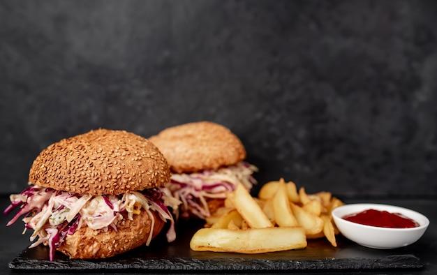 Dois hambúrgueres de rabo de boi com batata frita de repolho em uma mesa de pedra