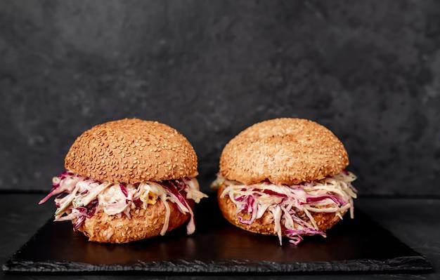 Dois hambúrgueres de rabo de boi e repolho em uma mesa de pedra