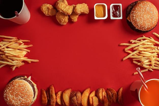 Dois hambúrgueres e batatas fritas, molhos e bebidas em fundo vermelho fast food vista superior plana leigos ...