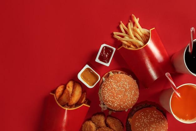 Dois hambúrgueres e batatas fritas, molhos e bebidas no fundo vermelho fast food vista superior plana leigos com ...