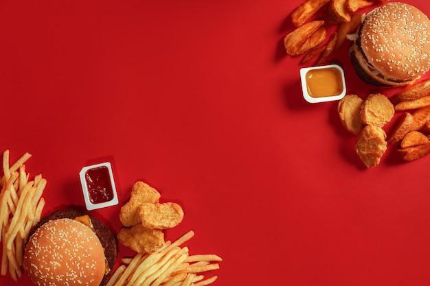 Dois hambúrgueres e molhos de batata frita em fundo vermelho vista superior do fast food
