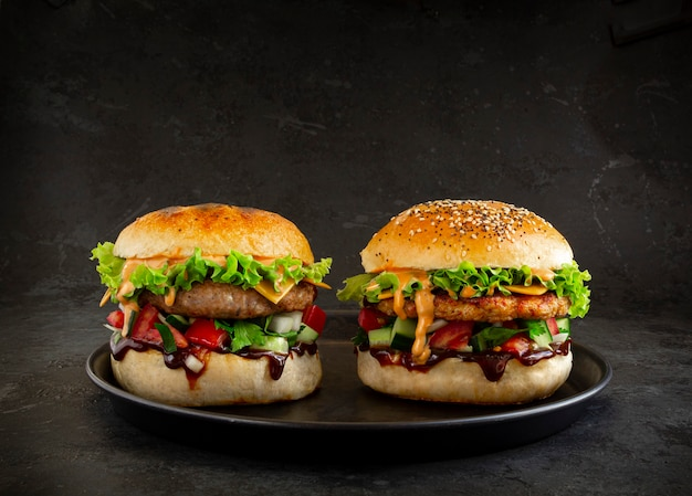 Dois hambúrgueres saborosos frescos em fundo escuro