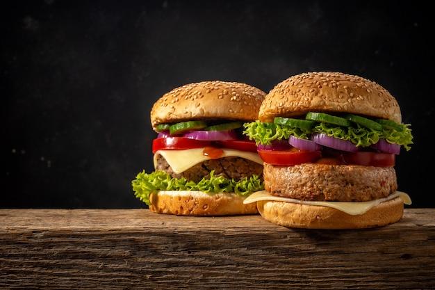 Dois hambúrgueres saborosos na mesa de madeira rústica