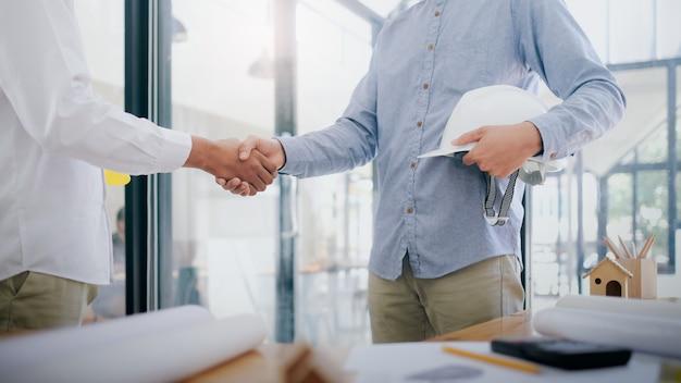 Dois handshaking de engenheiro civil ou arquiteto têm um mega projeto.