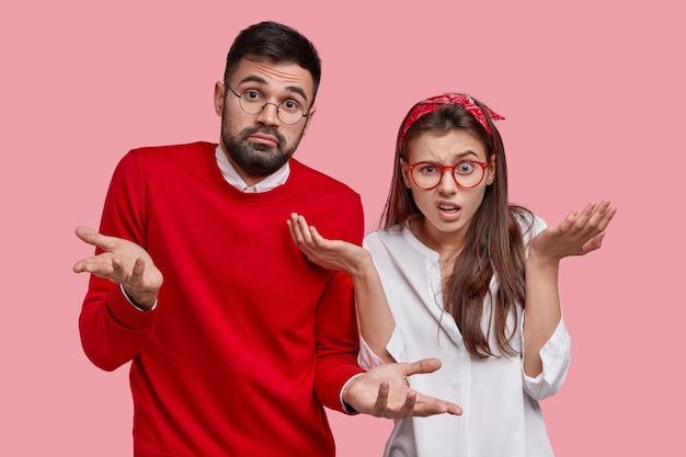 Dois hesitantes homem com a barba por fazer e uma mulher insatisfeita dão de ombros, sentem-se inseguros, têm dúvidas enquanto tomam decisões