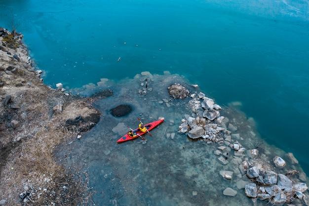 Dois homem atlético flutua em um barco vermelho no rio