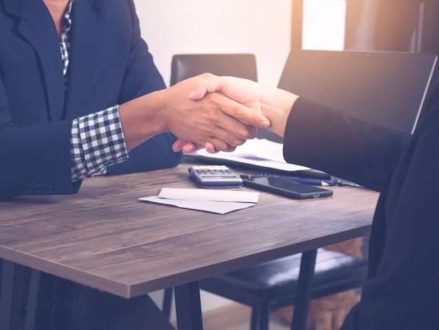 Dois homem de negócios e mulher que agitam a mão após negociar bem sucedido.