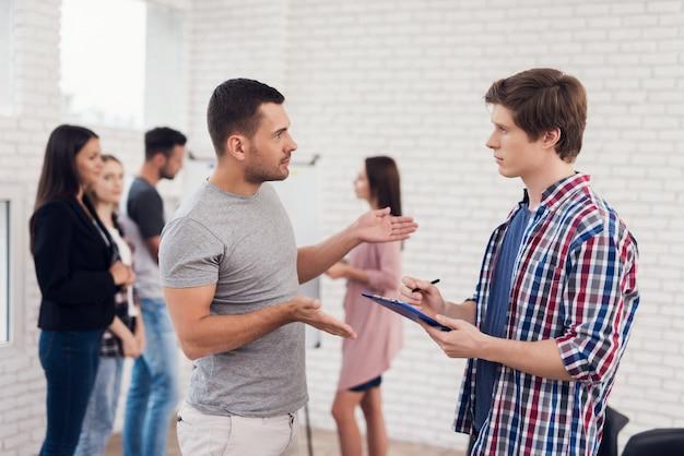 Dois homens adultos discutem negócios no encontro de pessoas criativas