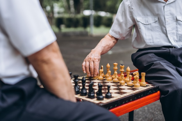 Dois homens adultos sêniors jogando xadrez no banco ao ar livre no parque.