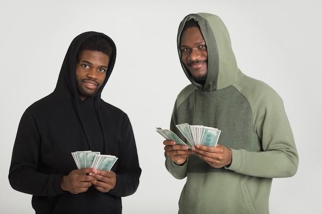 Dois homens africanos desportivos com fatos de treino num fundo branco com dólares