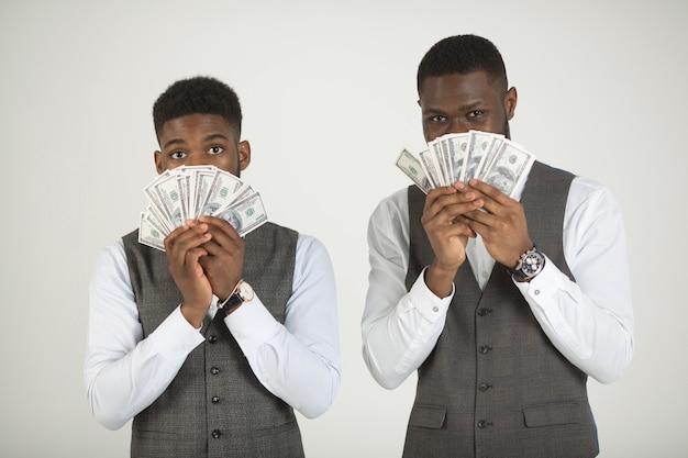 Dois homens africanos elegantes de terno em uma parede branca com dólares nas mãos