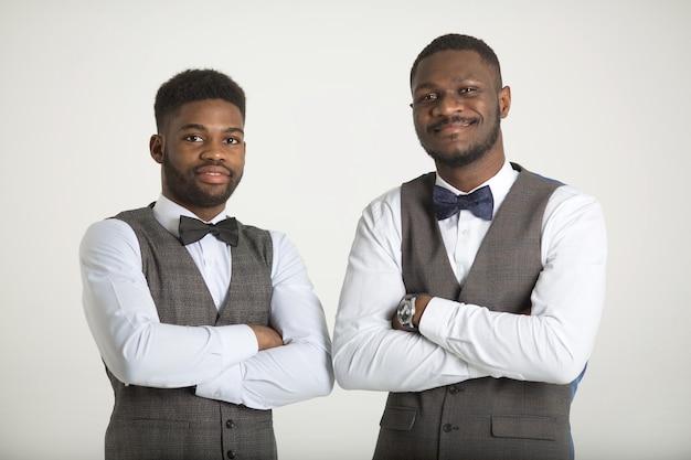 Dois homens africanos elegantes de terno na parede branca